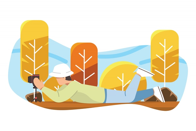 Photographer taking shots and lying down on the ground Premium Vector