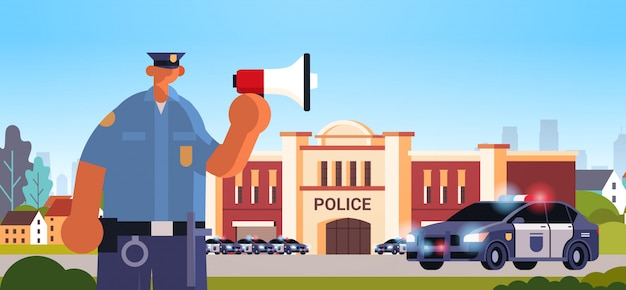 Policeman in uniform using loudspeaker making announcement security authority justice law service concept modern police station department building exterior portrait Premium Vector