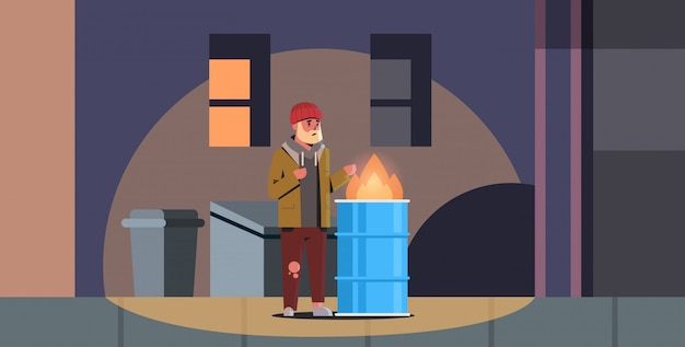 Poor bearded man warming his hands by fire beggar guy standing near burning garbage in barrel homeless jobless trash can city night street Premium Vector