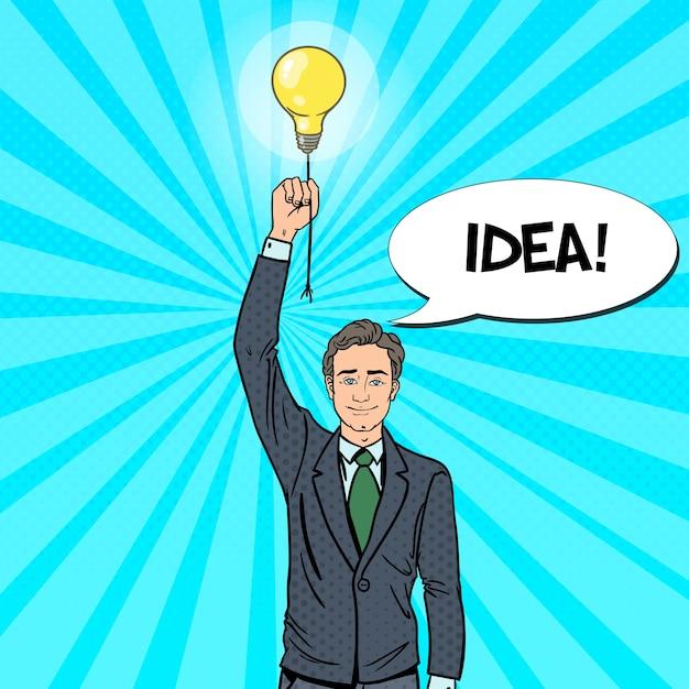 電球のアイデアを持つポップアート実業家。 Premiumベクター