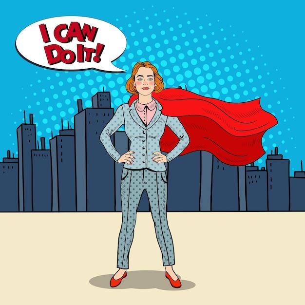 Поп-арт уверенная бизнес-леди супергерой в костюме с красной накидкой. Premium векторы