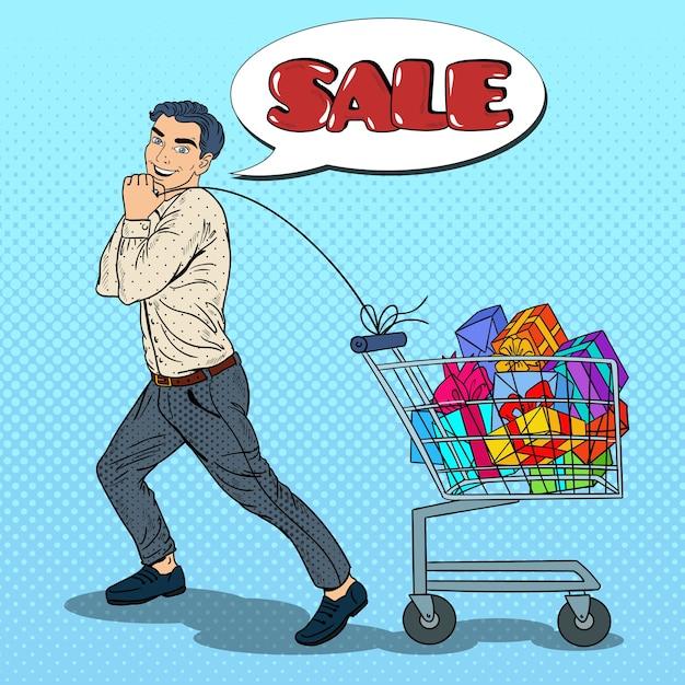 ショッピングカートと季節の販売のギフトがいっぱいのポップアート幸せな男。 Premiumベクター