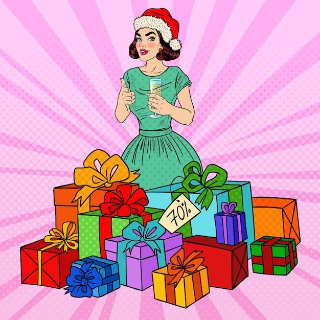Поп-арт счастливая женщина в шляпе санты с большими подарочными коробками и бокалом шампанского. Premium векторы
