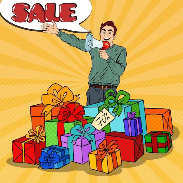 Поп-арт человек с мегафоном, продвигающий большие продажи, стоя в подарочных коробках. Premium векторы