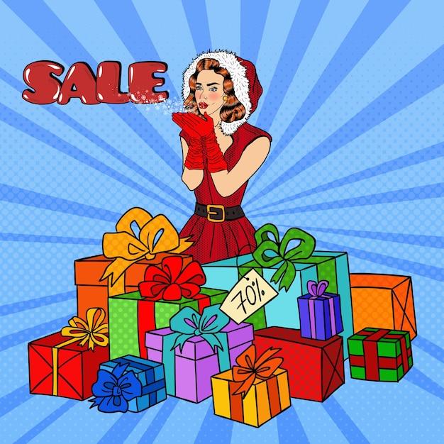 Поп-арт женщина в шляпе санта метель на рождественской распродаже. Premium векторы