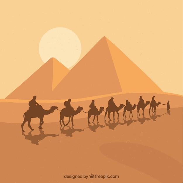 Pyramid landscape with caravan Free Vector