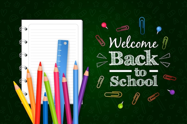 Realistic back to school background with pencils and notebook Free Vector