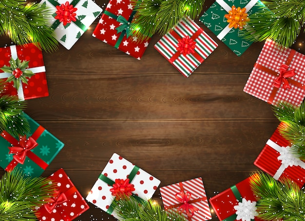 Realistic christmas background with colorful gift boxes and fir tree branches on wooden table Free Vector
