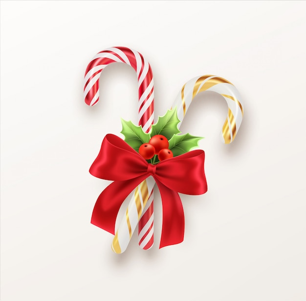 赤いリボンとクリスマスのヒイラギの小枝が付いている現実的なクリスマスキャンデー杖 Premiumベクター