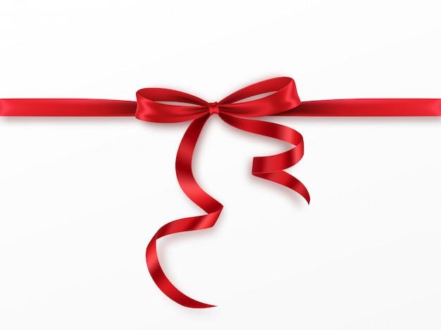 赤い弓と白い背景の上のリボン。リアルな赤の弓。 Premiumベクター
