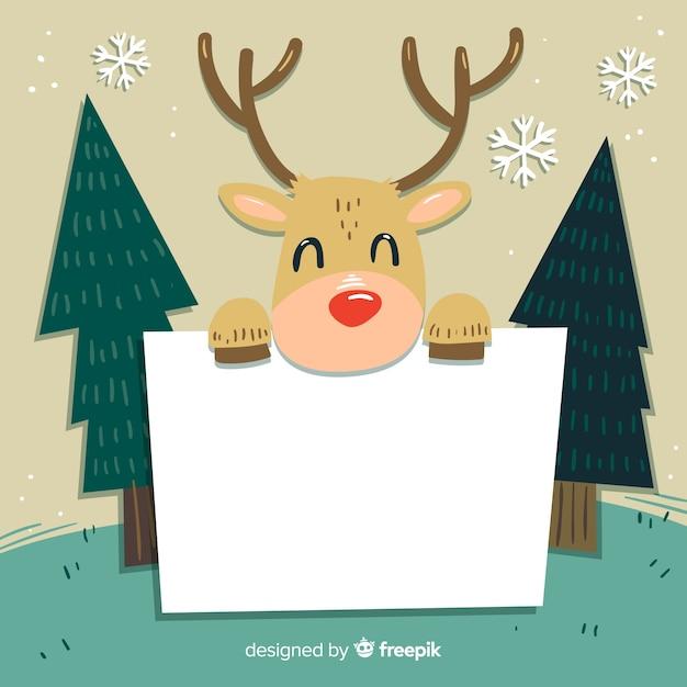 Reindeer holding blank sign background Free Vector
