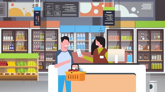 Retail woman cashier at checkout supermarket Premium Vector