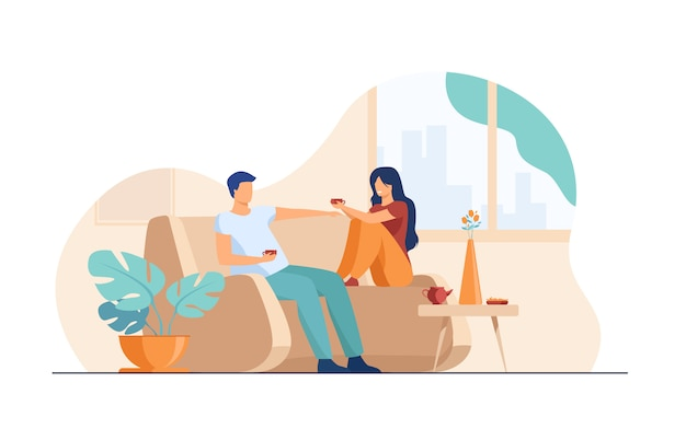 Romantic couple sitting at sofa, talking and drinking coffee Free Vector