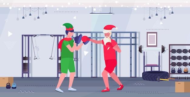 엘프 도우미 운동 건강한 라이프 스타일 크리스마스 휴일 축하 개념 현대 체육관 인테리어와 권투 연습을 연습 산타 클로스 복서 프리미엄 벡터