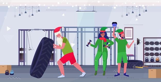 아령과 Kettlebell 훈련 운동 건강한 라이프 스타일 개념 크리스마스 새해 휴일 현대 체육관 인테리어와 운동 산타 클로스 뒤집기 타이어 엘프 프리미엄 벡터