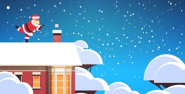 Santa claus on roof near chimney using fishing rod merry christmas  holiday concept winter snowfall  greeting card full length horizontal vector illustration Premium Vector