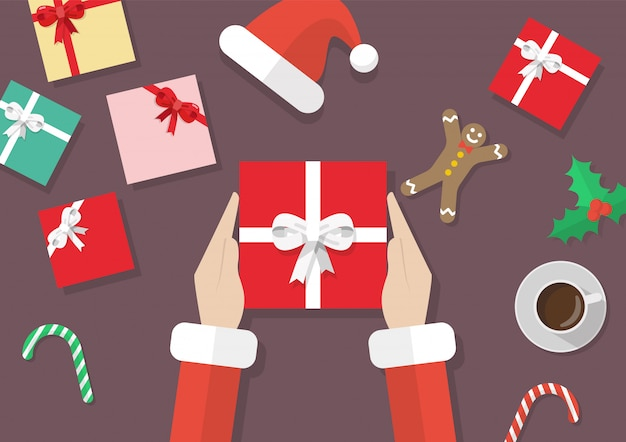 Santa hands holding gift box with christmas elements Premium Vector