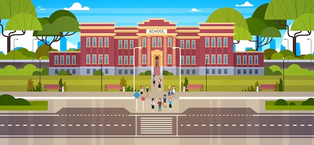 School building with group of pupils students on front yard with green grass and trees landscape Premium Vector