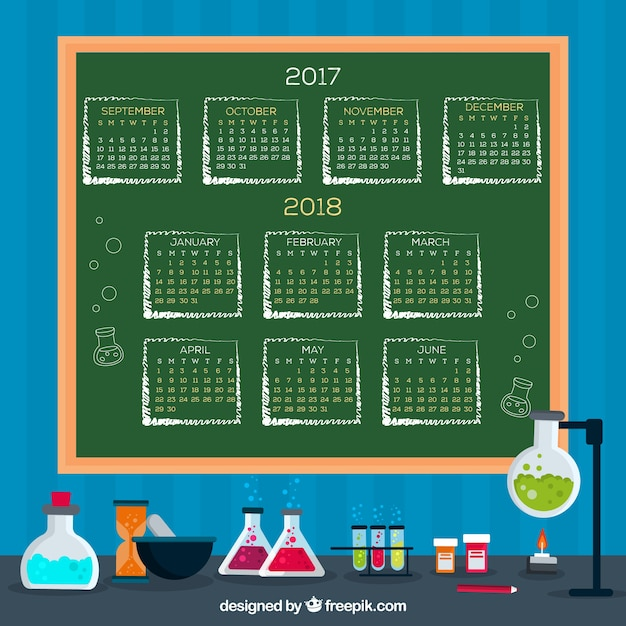School calendar on blackboard with science materials