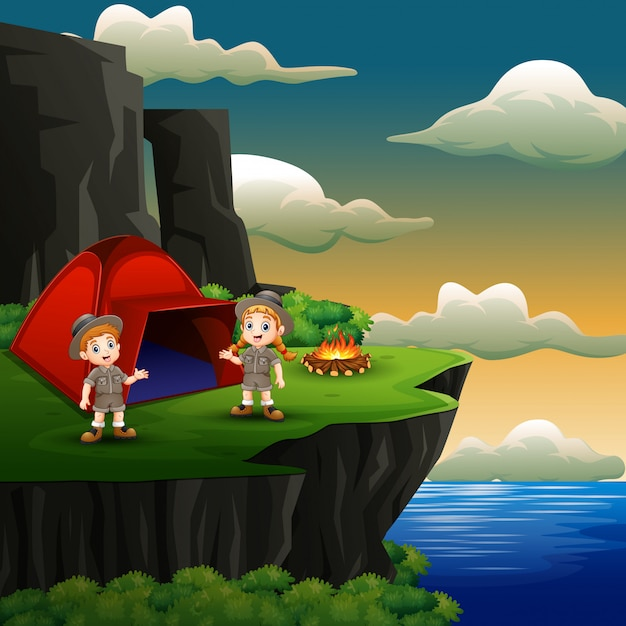 Scout boy and girl are camping on the cliff Premium Vector