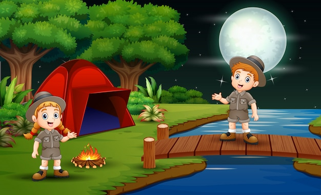 Scout boy and girl are camping in the nature at night Premium Vector