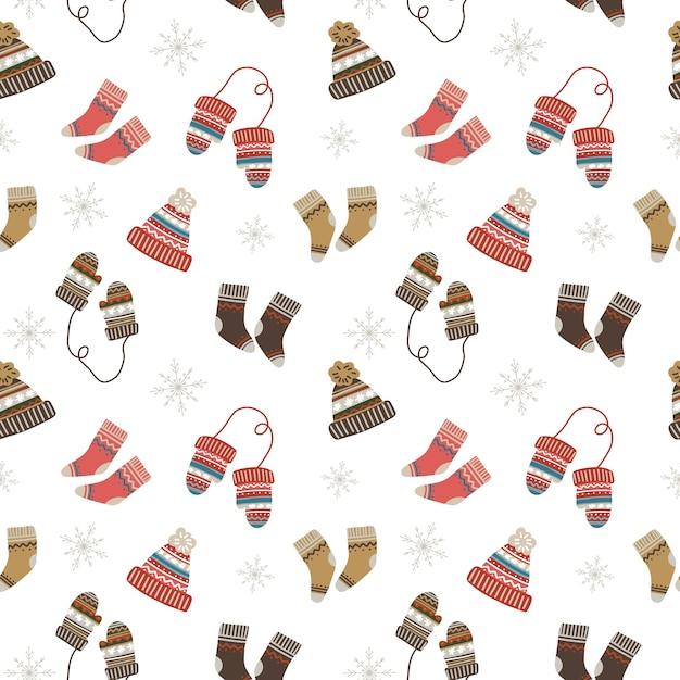 Бесшовный рождественский образец с уютными и теплыми носками, шапками и варежками Premium векторы