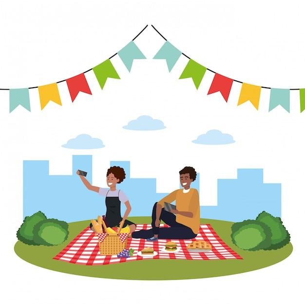 Selfieピクニックを取る千年夫婦のスマートフォン Premiumベクター