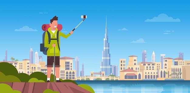 美しいドバイの街の背景の上にselfie写真を撮るバックパックと男の観光客 Premiumベクター