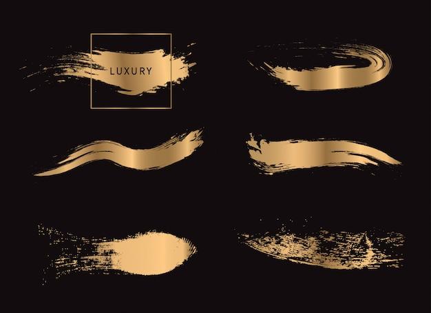 Set of gold paint brush strokes. Premium Vector