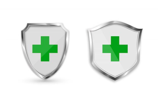 緑の十字架と医療健康保護シールドを設定します。 Premiumベクター