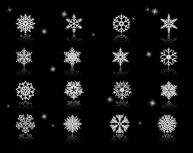 火花と黒の背景にさまざまな白い雪片アイコンのセット。 無料ベクター