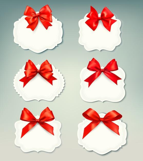Набор красивых ретро этикеток с красными подарочными бантами с лентами. Premium векторы