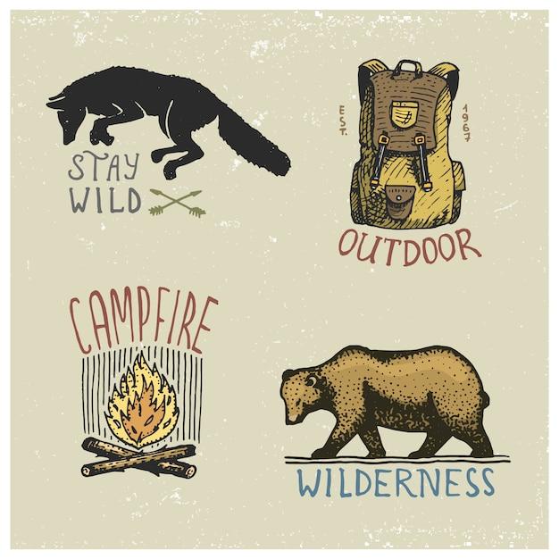 Набор гравированных винтажных, нарисованных от руки, старых, ярлыков или значков для кемпинга, походов, охоты с диким волком, медведя гризли, огненного огня, рюкзака Premium векторы