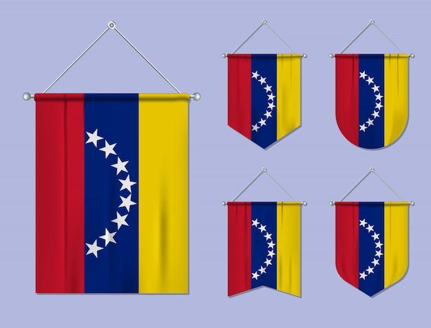 Набор висящих флагов венесуэлы с текстильной текстурой. разнообразие форм национального флага страны. вертикальный шаблон вымпела. Premium векторы