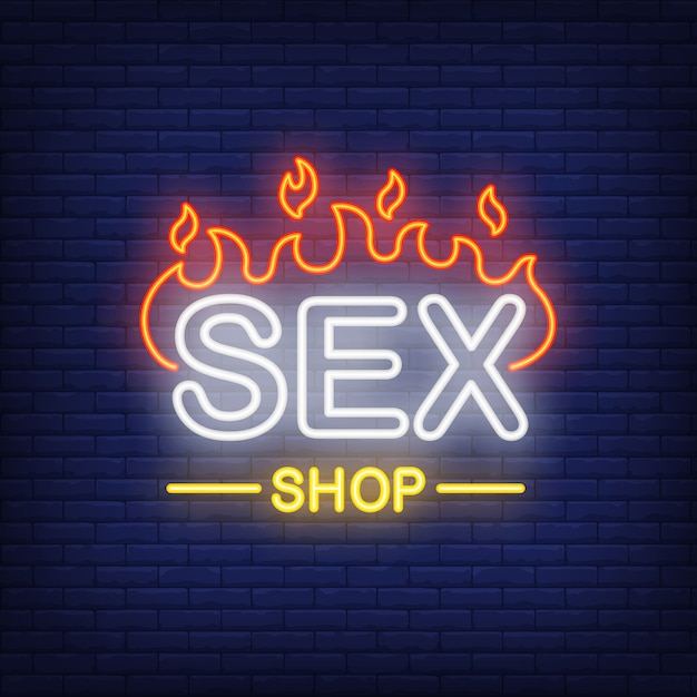 Sex shop lettering on fire. neon sign on brick background. Free Vector