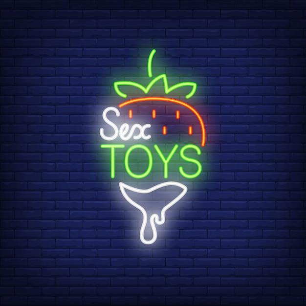 Клубника с надписью sex toys. неоновый знак на фоне кирпича. Бесплатные векторы