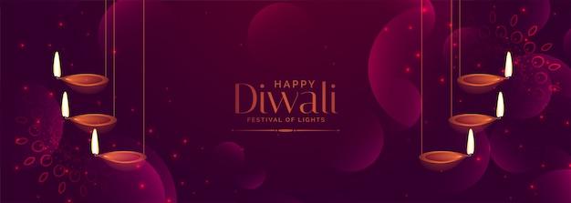 Shiny purple diwali festival banner with hanging diya Free Vector