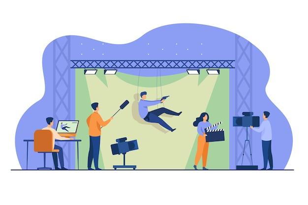 La squadra di tiro che filma la scena d'azione con l'acrobazia che cade e tiene la pistola su uno sfondo verde. illustrazione vettoriale per cinema, regia cinematografica, casting, concetto di stunt man Vettore gratuito