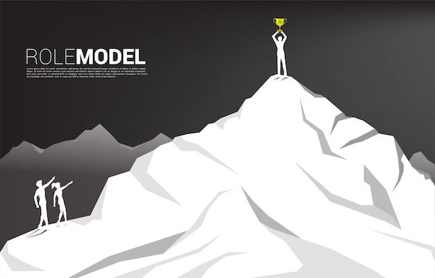 Silhouette of businessman and business woman point forward to businessman with trophy on top of mountain. concept of career start up and role model. Premium Vector