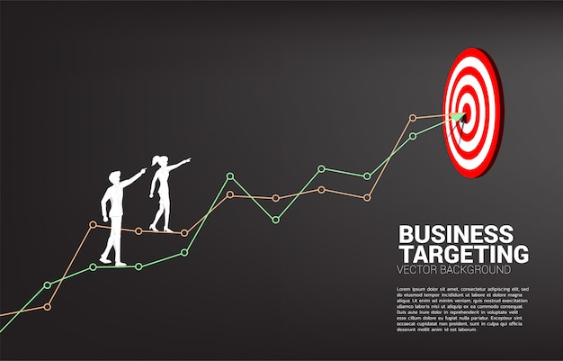 Silhouette of businessman and businesswoman point to dartboard on line graph to center of dartboard Premium Vector