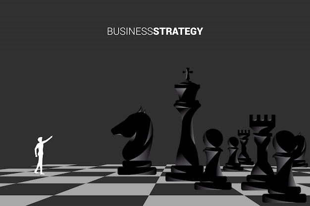 Silhouette of businessman point forward with chess piece. Premium Vector