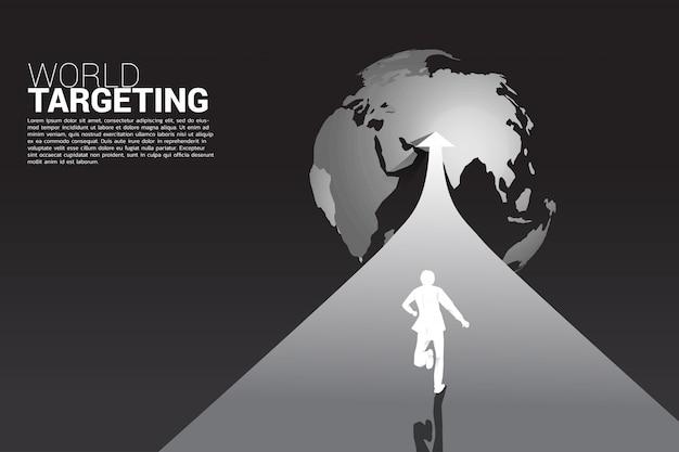 Silhouette of businessman running on arrow to world globe. Premium Vector