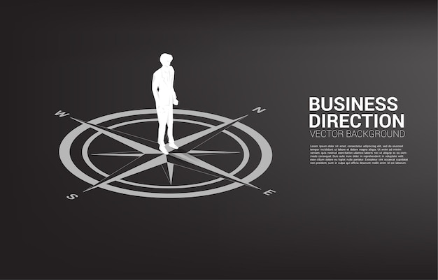 Silhouette of businessman standing at center of compass on floor. Premium Vector