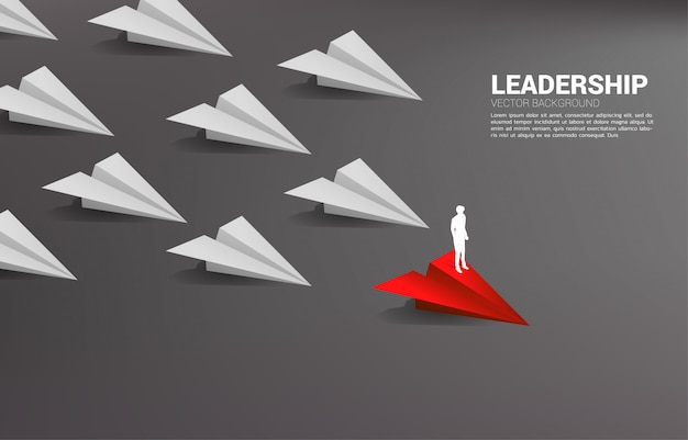 Silhouette of businessman standing on red origami paper airplane leading group of white. business co