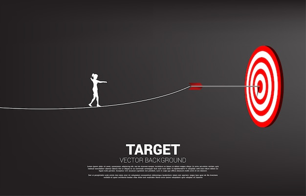 Silhouette of businesswoman walk rope to arrow archery hit on the center of target. concept of targeting and business challenge. Premium Vector