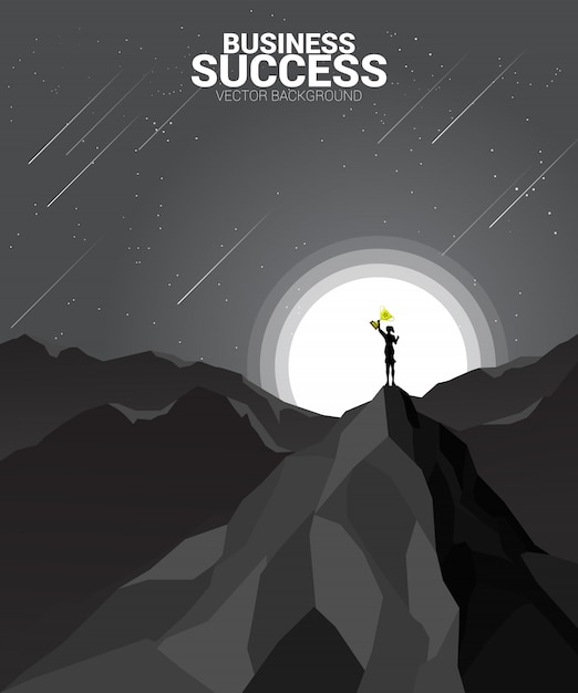 Silhouette of businesswoman with trophy on top of mountain. Premium Vector