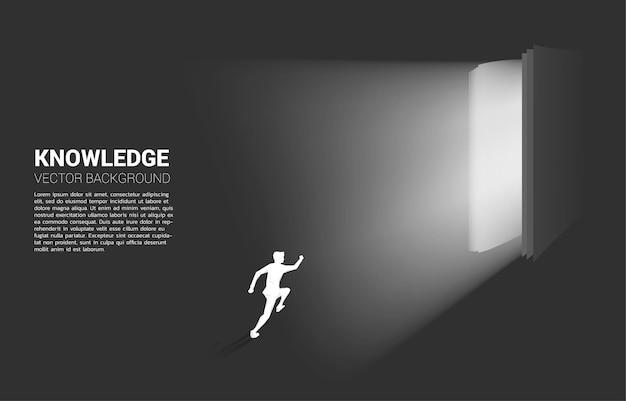 오픈도 서에서 빛에서 실행하는 사업가의 실루엣. 책 지식의 개념 프리미엄 벡터