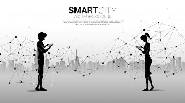 男と女のシルエットは、携帯電話を使用して5 g未来的なポリゴンドット接続線と都市の背景。自宅から離れた場所で仕事をするためのコンセプトとテクノロジー。 Premiumベクター