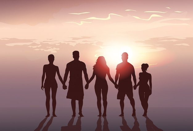 Silhouette people group stand holding hands man and woman full length over sunset background Premium Vector