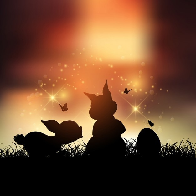 Silhouettes of Easter bunnies against a sunset\ sky